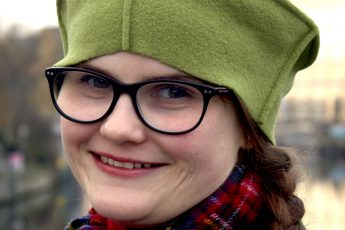 Vinie Walling smiling into the camera and wearing a green hat and tartan scarf